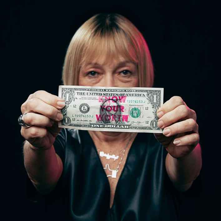 Cindy Gallop holding a dollar bill with the words