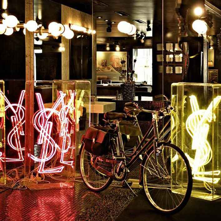 Bike and YSL neon lights at Cindy's Black Apartment.